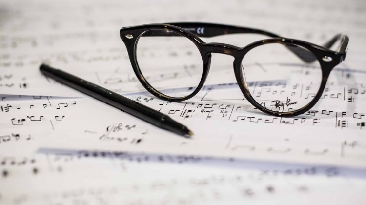 Pen and glasses on music notation pages